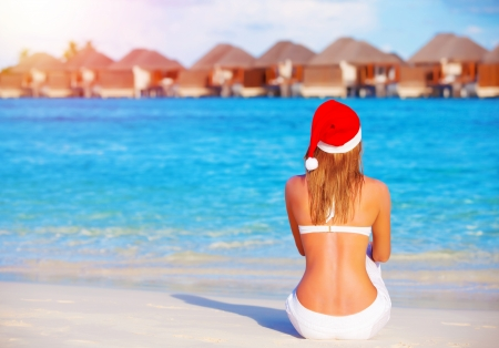 New Year celebration on Maldives, travel on winter holidays to summer destinations, back side, wearing red Santa Claus hat photo