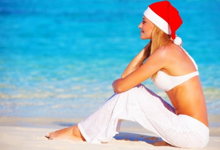 Christmas holidays on Maldives,  pretty female on the beach wearing Santa Claus hat, side view, travel and vacation concept photo