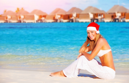 Christmas vacation on Maldives, pretty woman sitting on the beach, wearing red Santa hat, side view, luxury wintertime holidays concept photo
