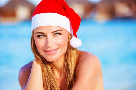 Closeup portrait of attractive blonde female wearing red Santa hat celebrating Christmas holidays on Maldives, exotic travel and vacation concept photo