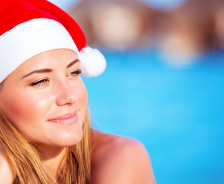 Portrait of pretty woman wearing red Santa hat, Christmastime holidays on the beach on exotic island, luxury winter time vacation concept photo