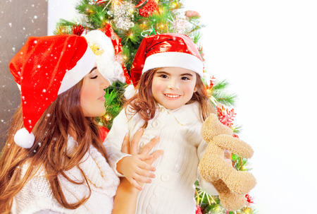 Happy family near beautifully decorated Christmas tree, young mother with cute daughter wearing red Santa hat, copy space, winter holiday photo