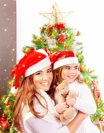 baby near christmas tree: Mother with daughter celebrate Christmas, pretty woman with baby girl near Xmas tree isolated on white background, happy New Year party at home