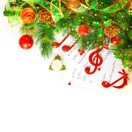 Festive musical still life, red treble clef and notes decorated fresh green fir tree branch isolated on white background, Christmas holidays concept