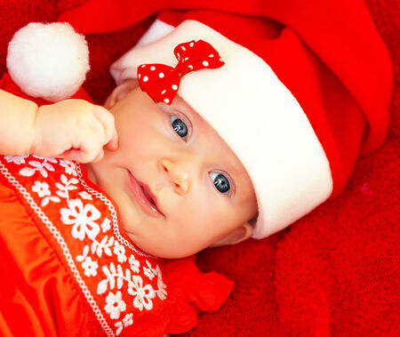 Closeup on beautiful newborn baby wearing red festive Christmas costume, Santa hat with decorative bow, New Year celebration photo