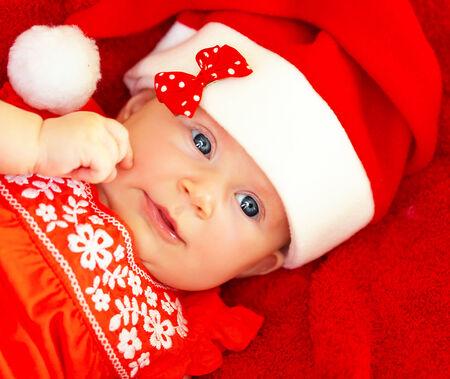 Closeup on beautiful newborn baby wearing red festive Christmas costume, Santa hat with decorative bow, New Year celebration Stock Photo - 23848396