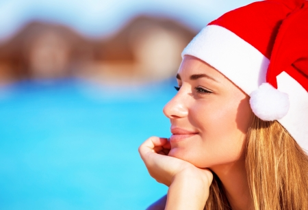 Portrait of pretty woman wearing red Santa hat and dreamy looking on side, Christmastime holidays on the beach on exotic island, luxury winter time vacation concept photo