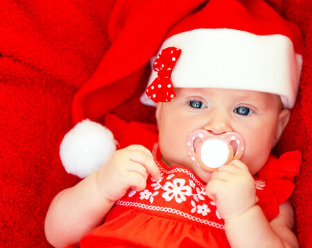Closeup portrait of adorable newborn girl with pacifier in mouth wearing red festive Santa hat, New Year celebration, Christmas holiday, happy childhood concept Stock Photo - 23848452