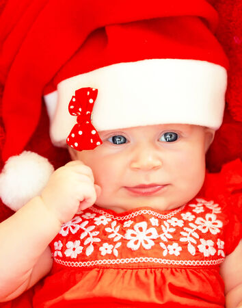 Closeup on beautiful newborn baby wearing red festive Christmas costume, Santa hat with decorative bow, New Year celebration Stock Photo - 23848455