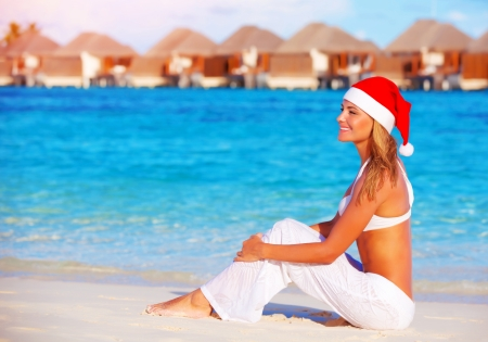 Beautiful young woman celebrating Christmas holiday on Maldive island, wearing red Santa hat, sitting on the beach, luxury resort photo