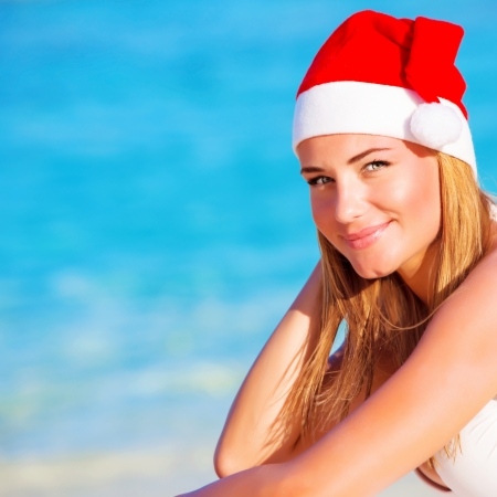 New Year vacation, happy blond girl enjoying Maldives, wearing red Santa hat, travel to exotic country on winter holidays, copy space photo