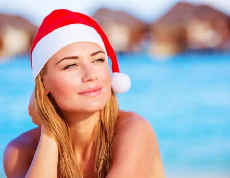beach happy new year: Closeup portrait of cute woman wearing red Santa hat, celebrating Christmas holidays on Maldive islands, New Year party on the beach Stock Photo