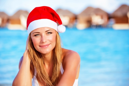 Closeup portrait of attractive blonde female wearing red Santa hat celebrating Christmas holidays on Maldives, exotic travel and vacation concept Stock Photo - 23848464