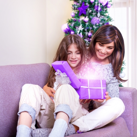 Young brunette mother with teen girl opening Christmas present, excited faces, magical glowing light from gift box, happiness and excitment concept photo