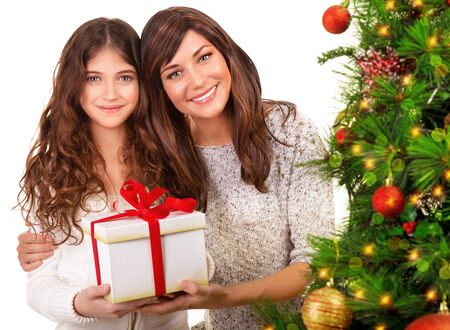 Closeup portrait of attractive mother with cute daughter holding in hands festive gift box, beautiful decorated Christmas tree, copy space photo