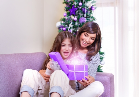 Excited mother with daughter sitting at home near beautiful decorated Christmas tree, enjoying magical gift box, New Year fairy tale concept photo