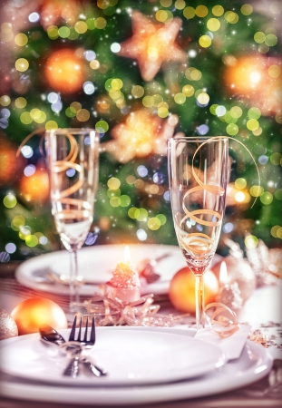 new year eve: Closeup photo on festive dinner still life, festive table setting on luxury decorated Christmas tree background, New Year eve concept Stock Photo