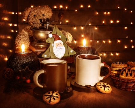 shining light: Christmas still life, tasty traditional dessert, two cups of coffee with tasty cookie, teddy bear and little decorative Xmas tree toy with Santa Claus face Stock Photo