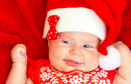 Sweet newborn baby wearing red Santa hat on Christmastime holidays, Christmas hat, New Year fun, funny facial expression, happy childhood concept photo