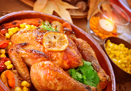holiday food: Closeup on tasty roasted chicken with vegetables on the table, traditional food of Thanksgiving day, autumnal holiday concept