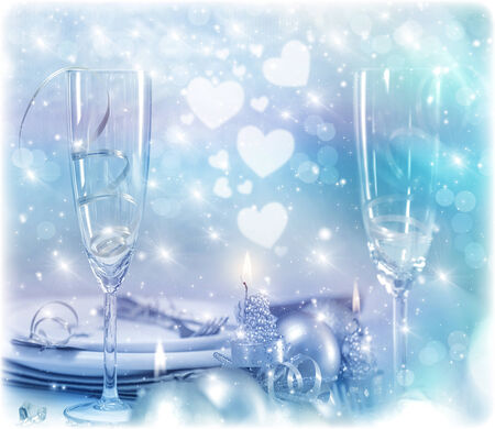 christmas eve: Festive romantic table setting, Christmas eve in restaurant, white utensil served with silver cutlery, candle light and decorative shiny baubles Stock Photo