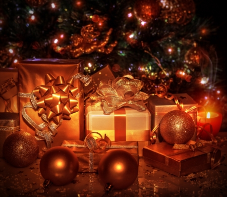 new year eve: Many different gift boxes wrapped in shiny golden paper under decorated Christmas tree, Christmastime surprises, New Year eve concept