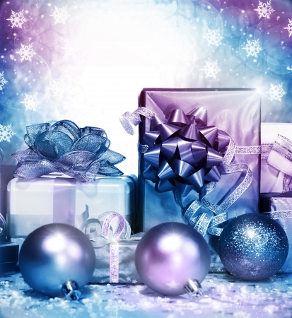 Photo of silver Christmas presents on falling snowflake background, different gift box wrapping in shiny paper and decorated with ribbon bow, New Year surprise, festive greeting card photo