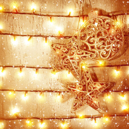 Golden Christmas baubles hanging on wooden door, decorated with glittering garland, New Year eve magic, beautiful Xmas still life, glowing background photo