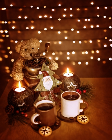 Christmastime decoration, beautiful festive still life on the table on glowing wall background, cups of tea with traditional Christmas gingerbread photo