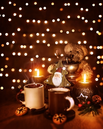 Christmas still life on the table at home, mugs with coffee and cookies, decorative Christmas tree, teddy bear, festive glowing background photo
