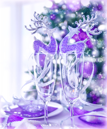 noel: Little beautiful reindeer toy decorate wineglasses on festive table, traditional Christmas ornament, winter holiday celebration in the restaurant
