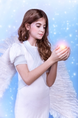 Cute Christmas angel on blue snowy background, adorable girl with candle in hands, religious winter holiday, peace and harmony concept photo