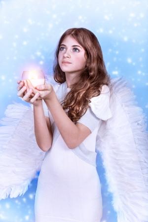 Leuke kerst engel op blauwe besneeuwde achtergrond, schattig meisje met kaars in handen, religieuze winter vakantie, vrede en harmonie-concept Stockfoto