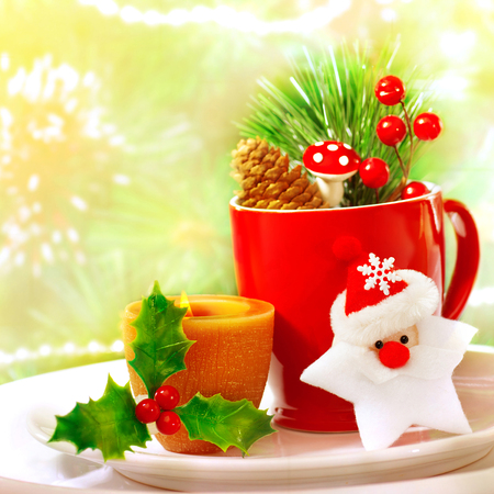 Border of Christmastime utensil set, red tea cup standing on white plate and decorated with Santa Clause star toy, yellow candle, twig of berry, fir cone and branch of Christmas tree, holiday dinner photo