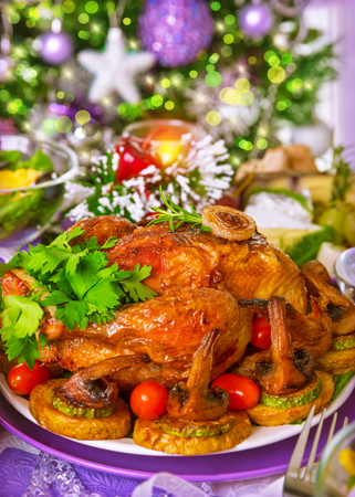 Closeup on tasty oven baked chicken on centerpiece of festive table in Christmas eve, celebrating holidays at home concept photo