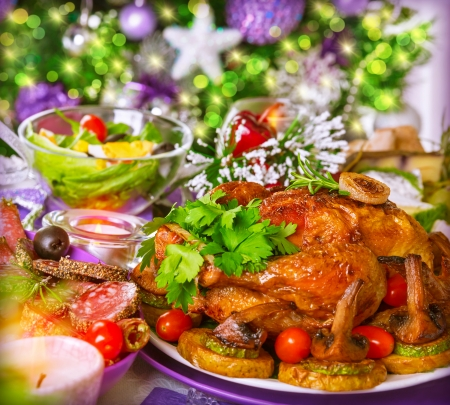 Traditional Christmas table on decorated Xmas tree background, delicious roasted chicken with baked vegetables, New Year festive table setting