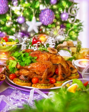 Traditional Christmas table on decorated Xmas tree background, delicious roasted chicken with baked vegetables, New Year festive table setting  photo