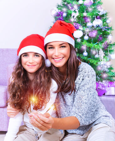 christmas eve: Portrait of young mother with teenage daughter burning bengal fire at home, having fun on Christmas eve, New Year celebration concept