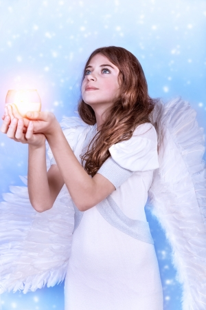 Beautiful angel praying, looking up, holding in hands candle, isolated on blue snowy background, Christmas holiday, purity and innocence concept photo