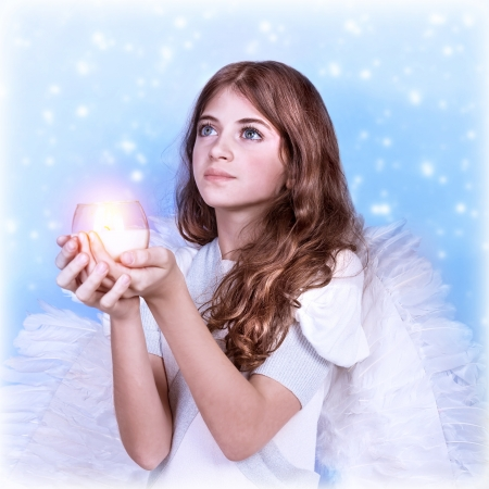 Closeup portrait of cute little angel looking up, holding candle in hands and praying to God, snow falling background, Christmas costume party photo