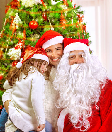 Christmas party, happy family at home celebrating New Year, mother with daughter and Santa claus near Xmas tree, happiness concept Stock Photo - 24262551