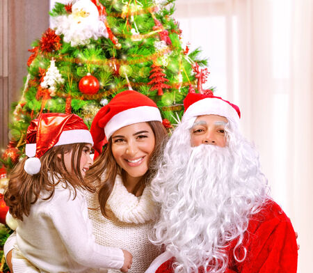 Christmas party, happy family at home celebrating New Year, mother with daughter and Santa claus near Xmas tree, happiness concept photo
