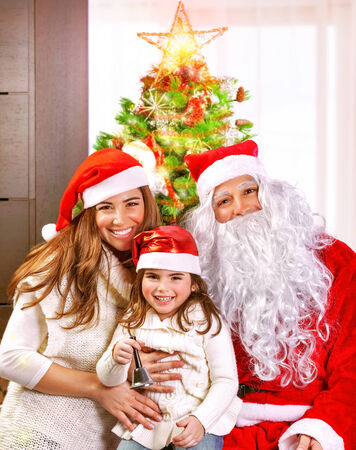 Happy cheerful young family celebrate Christmas holiday at home, little girl with mother and father wearing Santa Claus costume Stock Photo - 24262553