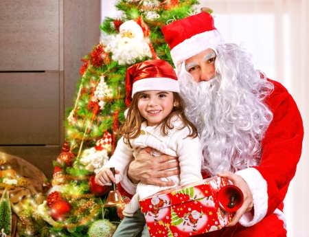 Portrait of little girl receive gift box from Santa Claus, sitting near decorated Christmas tree, happy childhood, Christmastime children's party Stock Photo - 24262555