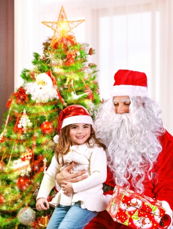 Portrait of little girl receive gift box from Santa Claus, sitting near decorated Christmas tree, happy childhood, Christmastime children's party  Stock Photo - 24262556