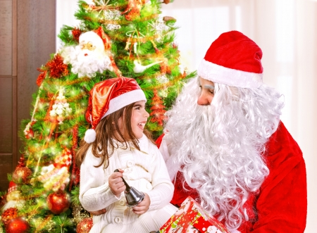Cute little girl with Santa Claus near Christmas tree at home, having fun, laughing and ringing festive bell, enjoying New Year party Stock Photo - 24262557