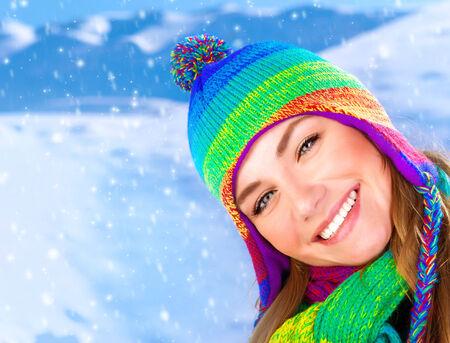 Feliz niña en el parque de invierno, sonriendo retrato de una mujer joven con sombrero colorido, hermoso primer plano de la cara, mujer bonita disfrutando de la nieve en las montañas, el invierno divertido concepto, la gente feliz al aire libre