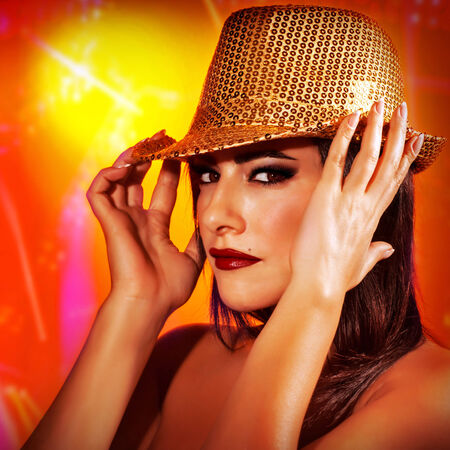 Closeup portrait of beautiful woman wearing golden shiny hat on red background, disco club, New Year celebration, fashion concept photo