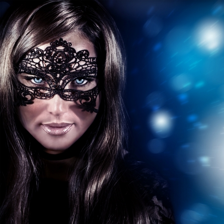 Closeup portrait of beautiful stylish woman wearing mask, luxury New Year party, masquerade in Christmas eve, beauty and fashion concept photo