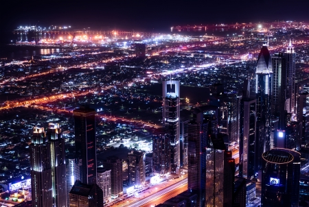 bird eye view: Dubai city at night, UAE, beautiful bird eye view on glowing downtown, panoramic cityscape, luxury arabic buildings, travel and tourism concept